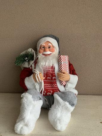 Kerstman zittend stof rode jas grijze broek met cadeautje benen buigzaam 50 cm | Home Sweet Home